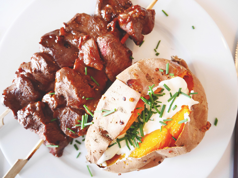 Baked sweet potatoes with feta cheese cream and meat skewers